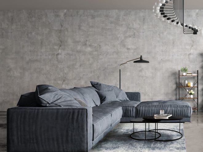 Modern interior design of a living room in an apartment, house, office, comfortable sofa, bright modern interior details and light from the window on the background of a concrete wall and floor with reflection.